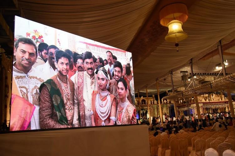 Telão mostra a família durante o casamento na Índia (Foto: AFP)