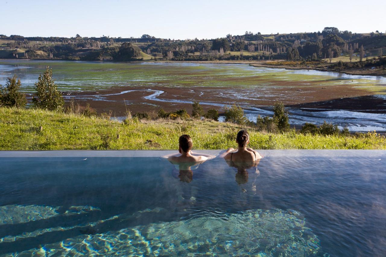 Casal descansa em piscina do hotel de luxo Tierra Chiloé, no Chile (Divulgação)
